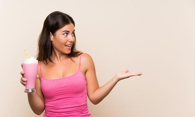 Giovane donna con frappè alla fragola con espressione facciale a sorpresa