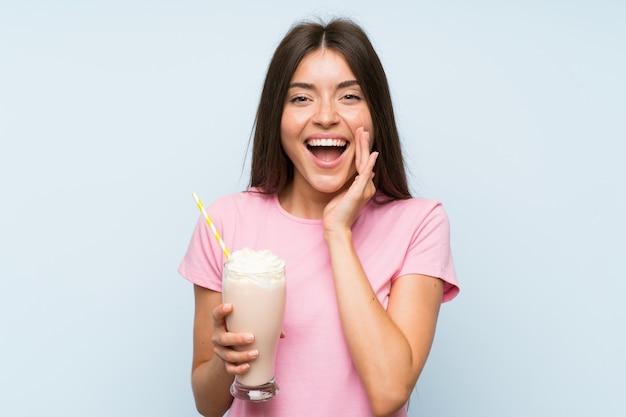Giovane donna con frappè alla fragola con espressione facciale sorpresa e scioccata
