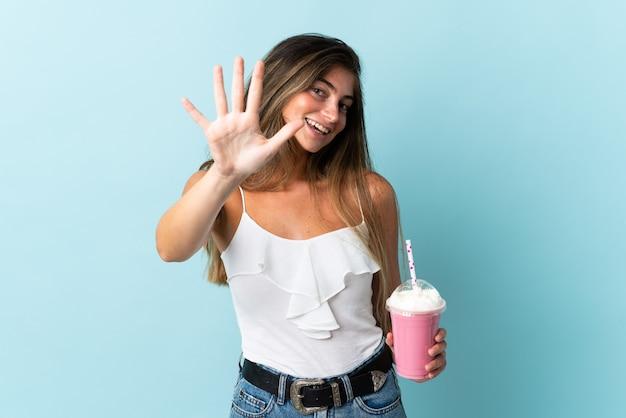 Giovane donna con frappè alla fragola isolato su blu contando cinque con le dita