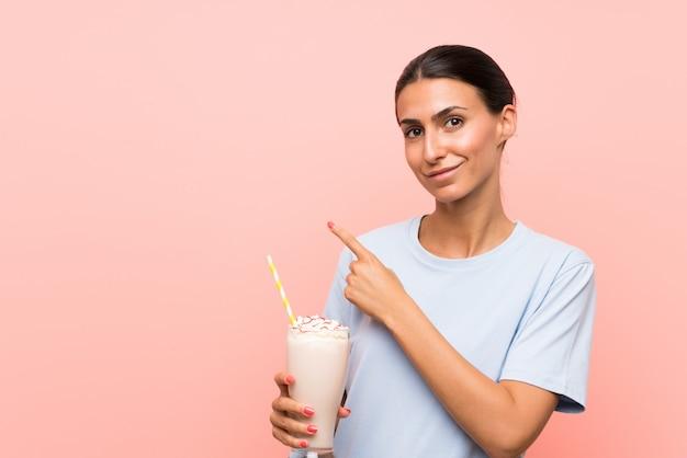 Giovane donna con frappè alla fragola sopra la parete rosa isolata che indica il lato per presentare un prodotto