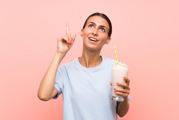 Giovane donna con frappè alla fragola sopra la parete rosa isolata che intende realizzare la soluzione mentre sollevando un dito su