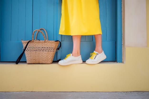 Giovane donna con gambe sexy e vestito giallo a parete blu