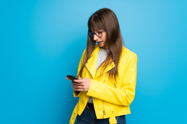 Giovane donna con giacca gialla su blu inviando un messaggio con il cellulare