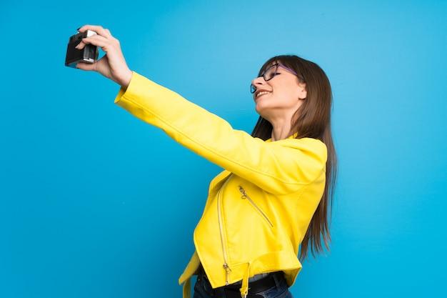 Giovane donna con giacca gialla sul blu in possesso di una macchina fotografica