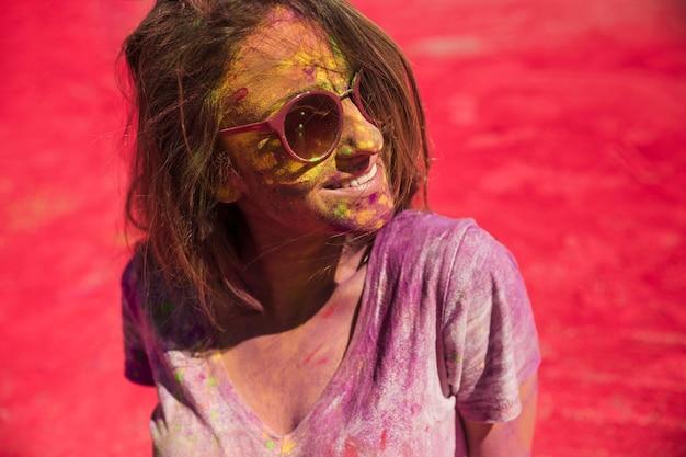 Giovane donna con gli occhi chiusi coperti di polvere che si trova sul colore rosso holi