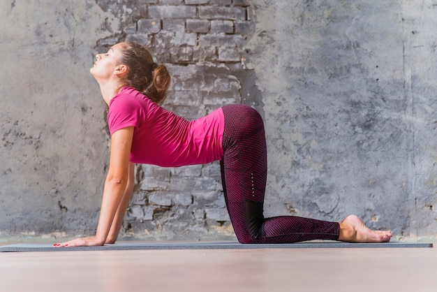 Giovane donna con gli occhi chiusi, praticare lo yoga di fronte al muro grigio danneggiato