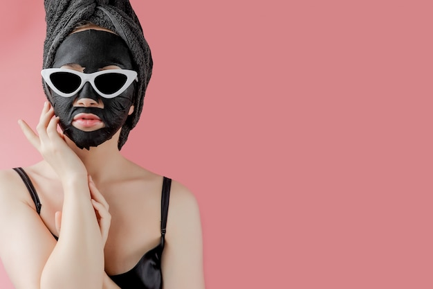 Giovane donna con gli occhiali che appling la maschera facciale nera del tessuto cosmetico su fondo rosa. maschera peeling viso con carbone, trattamenti di bellezza spa, cura della pelle, cosmetologia. avvicinamento