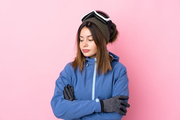Giovane donna con gli occhiali da sci sul muro rosa