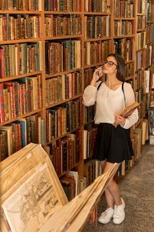 Giovane donna con gli occhiali parlando sul telefono e tenendo il libro