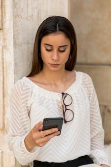 Giovane donna con gli occhiali sulla camicetta usando smartphone