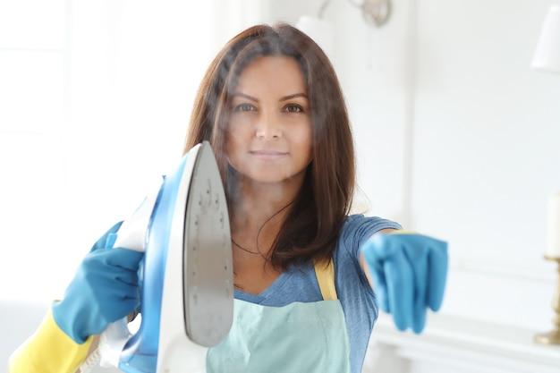 Giovane donna con guanti di gomma, pronta per stirare