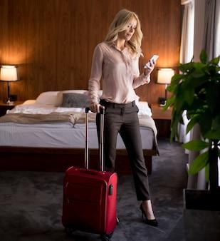 Giovane donna con i bagagli nella camera degli hotel