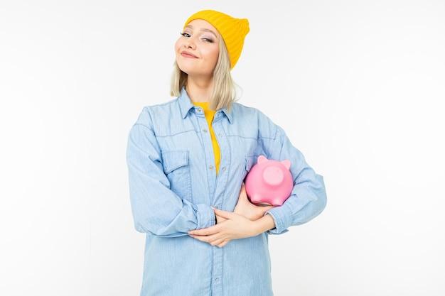 Giovane donna con i capelli bianchi in una camicia blu con una banca per il risparmio delle finanze su uno studio bianco con spazio di copia