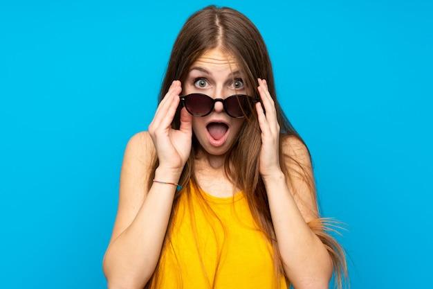 Giovane donna con i capelli lunghi con gli occhiali e sorpreso