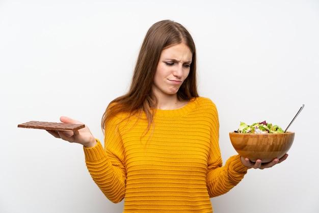 Giovane donna con i capelli lunghi con insalata