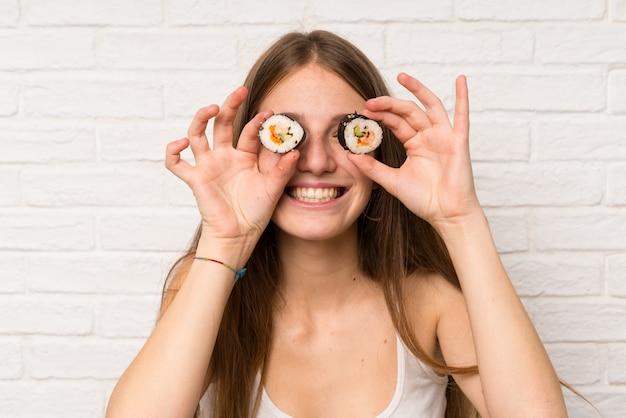 Giovane donna con i capelli lunghi mangiare sushi