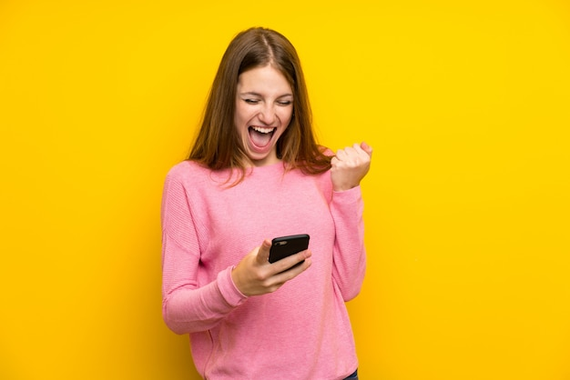 Giovane donna con i capelli lunghi sopra isolato muro giallo con il telefono in posizione di vittoria