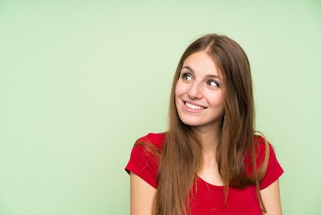Giovane donna con i capelli lunghi sopra muro verde isolato ridendo e alzando lo sguardo