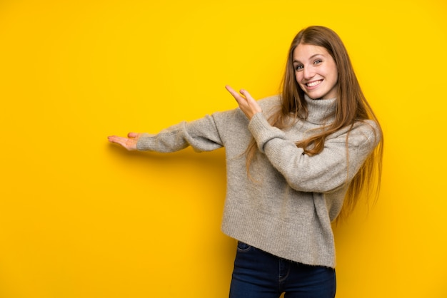 Giovane donna con i capelli lunghi su giallo che estende le mani sul lato per invitare a venire