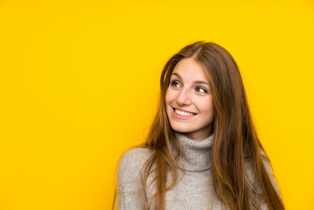 Giovane donna con i capelli lunghi su sfondo giallo ridendo e alzando lo sguardo