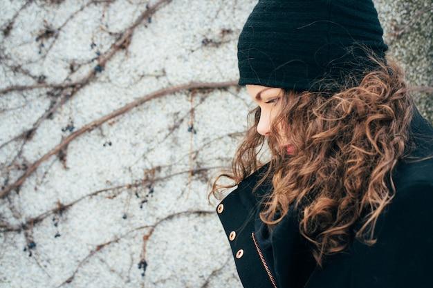 Giovane donna con i capelli ricci in un cappotto e berretto a piedi lungo la strada
