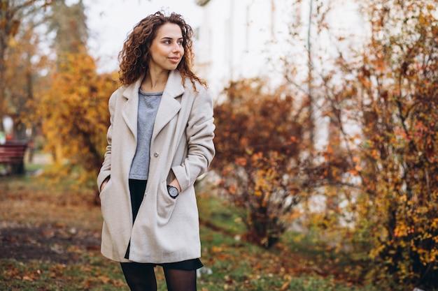 Giovane donna con i capelli ricci nel parco