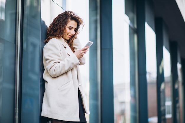 Giovane donna con i capelli ricci utilizzando il telefono in strada