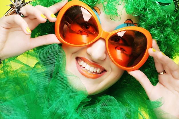 Giovane donna con i capelli verdi e occhiali carnaval