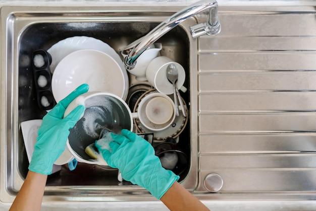 Giovane donna con i guanti lavare i piatti in cucina