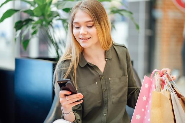 Giovane donna con i sacchetti della spesa facendo uso del suo smart phone per acquistare