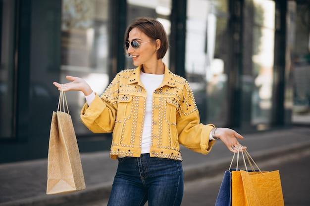 Giovane donna con i sacchetti della spesa in città