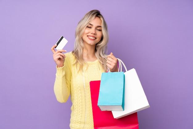 Giovane donna con i sacchetti della spesa sopra isolato