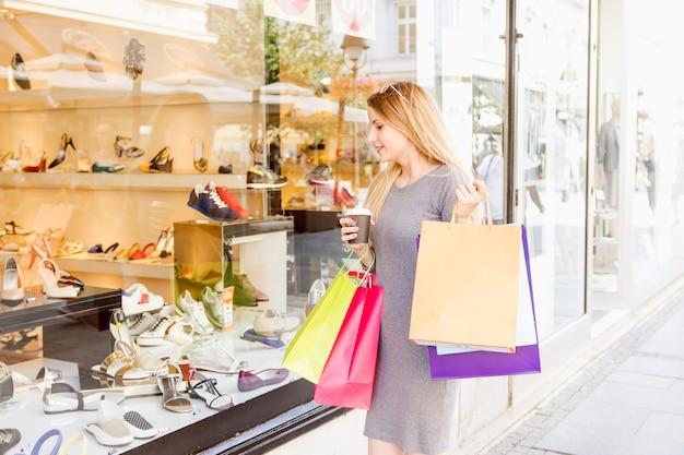 Giovane donna con i sacchetti della spesa variopinti che fa l'acquisto della visualizzazione della finestra