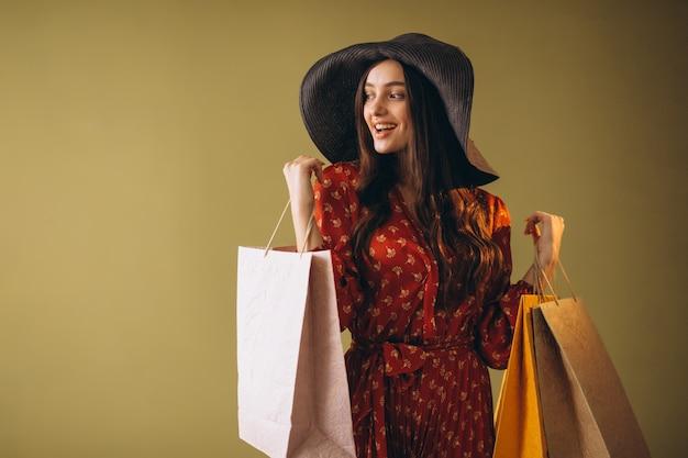 Giovane donna con i sacchetti di shopping in un bel vestito e cappello