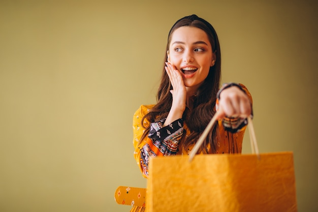 Giovane donna con i sacchetti di shopping in un bel vestito