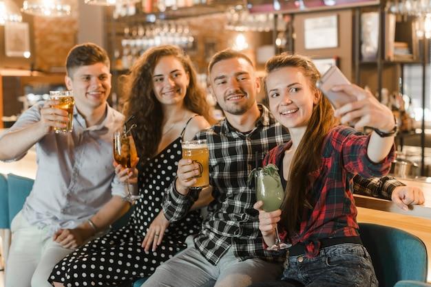 Giovane donna con i suoi amici in possesso di bevande prendendo selfie