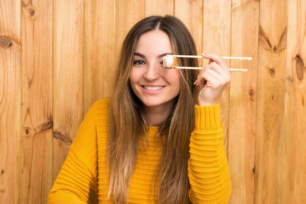 Giovane donna con i sushi sopra priorità bassa di legno