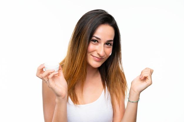 Giovane donna con idratante sopra la parete bianca isolata