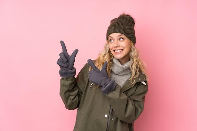 Giovane donna con il cappello di inverno isolato sulla parete rosa che indica con il dito indice una grande idea
