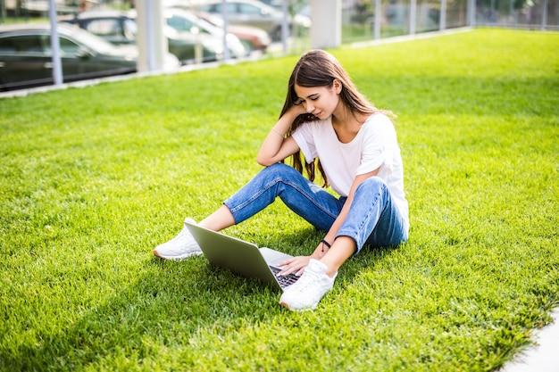 Giovane donna con il computer portatile che si siede sull'erba verde e che osserva ad un'esposizione