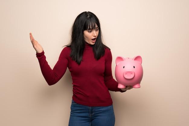 Giovane donna con il dolcevita rosso sorpreso mentre si tiene un piggybank