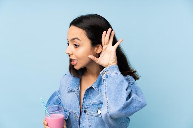 Giovane donna con il frappé della fragola sopra la parete blu isolata che ascolta qualcosa mettendo la mano sull'orecchio