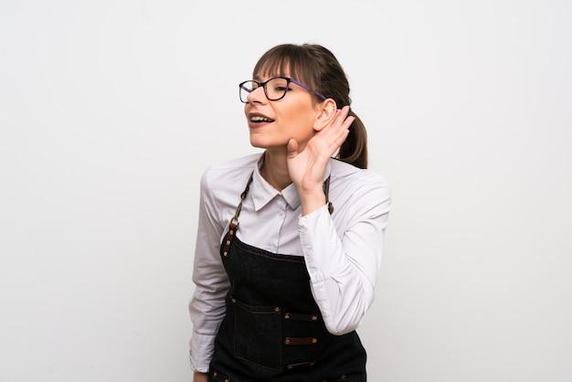 Giovane donna con il grembiule che ascolta qualcosa mettendo la mano sull'orecchio