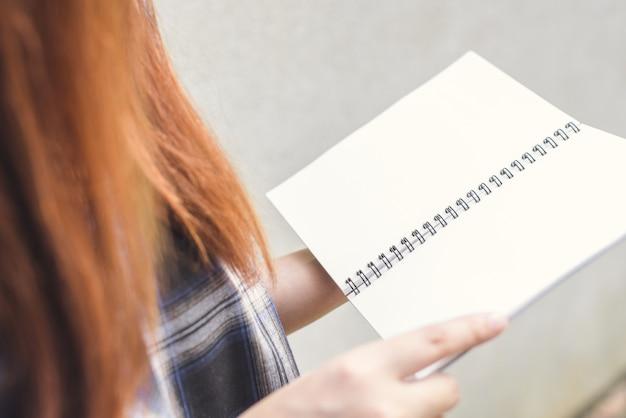 Giovane donna con il libro di lettura dei capelli castani, le mani in possesso di libro aperto, le foto di stile d'effetto vintage.