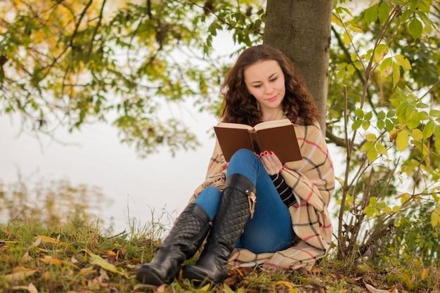 Giovane donna con il libro nel parco in autunno