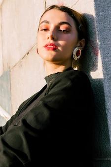 Giovane donna con il make-up che indossa orecchini rossi guardando la fotocamera