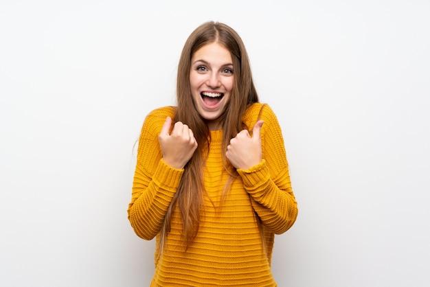 Giovane donna con il muro bianco isolato più giallo che celebra una vittoria