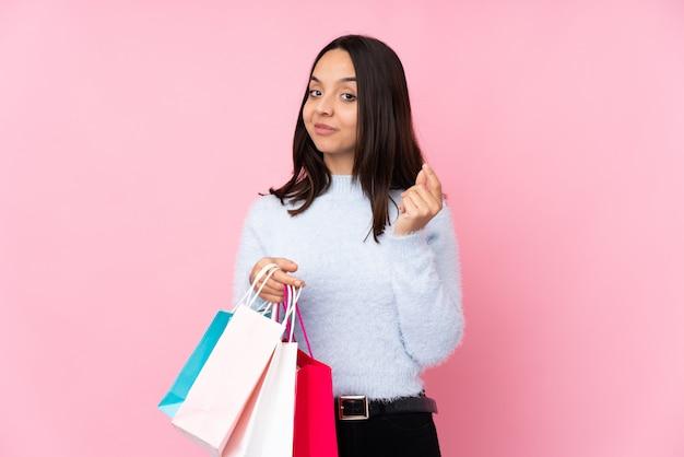 Giovane donna con il sacchetto della spesa sopra la parete rosa isolata che fa gesto dei soldi