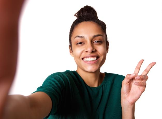 Giovane donna con il segno della mano di pace prendendo selfie