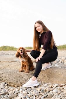 Giovane donna con il suo cane carino all'aperto